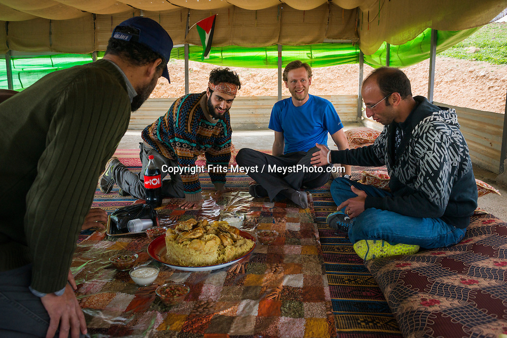 Palestine, March 2015. Hikers arrive at the Auja Bedouin camp where they have dinner and stay for the night in the homestay. The Abraham Path is a long-distance walking trail across the Middle East which connects the sites visited by the patriarch Abraham. The trail passes through sites of Abrahamic history, varied landscapes, and a myriad of communities of different faiths and cultures, which reflect the rich diversity of the Middle East. Photo by Frits Meyst / MeystPhoto.com for AbrahamPath.org