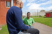 A 'listener' with another prisoner in the grounds of the prison. HMP The Mount, Bovingdon, Hertfordshire
