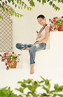 Woman sitting on wall in garden using mobile phone.