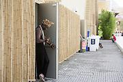 Man dressed in costume chat by his smartphote in a break of exhibition at a back door of Angola pavilion in Expo 2015, Rho-Pero, Milan. &copy; Carlo Cerchioli<br /> <br /> Un uomo in costume di scena chatta con il suo smartphone in una pausa dell'esibizione ad una porta sul retro del padiglione dell'Angola, Expo 2015, Rho-Pero, Milano.