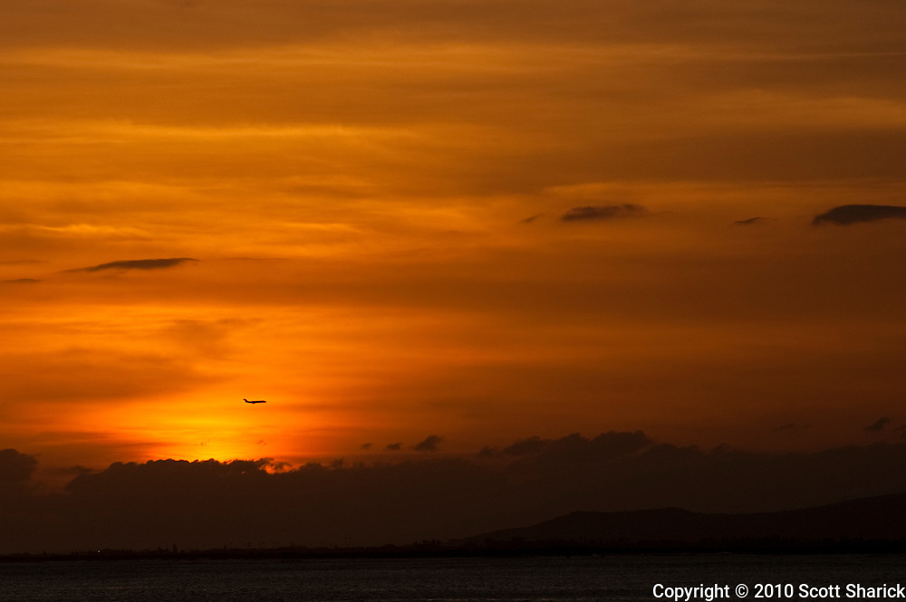 An airplane is silhouetted in the distance by a fire-red sky at sunset.