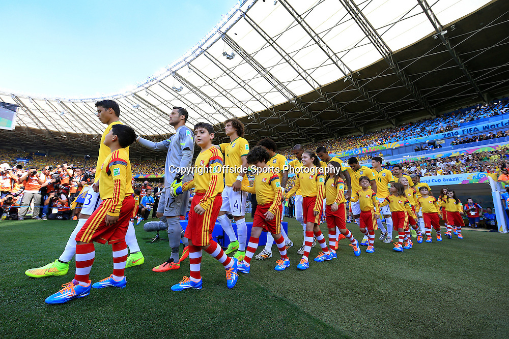 28th June 2014 - FIFA World Cup - Round of 16 - Brazil v Chile - Brazil players walk out alongside their mascots - Photo: Simon Stacpoole / Offside.