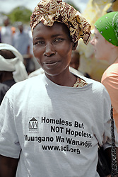 A woman at the World Social Forum opening march shows a slogan from the emerging Kenyan Federation, Muungano wa Wanavijiji, that was originally formed by residents of informal settlements at the peak of forced evictions and land grabbing in 1996. Muungano works with the urban poor who are victims of eviction, to advocate for their rights and to resist forced evictions or land grabbing.<br /> VII World Social Forum, at Nairobi city, Kenya.