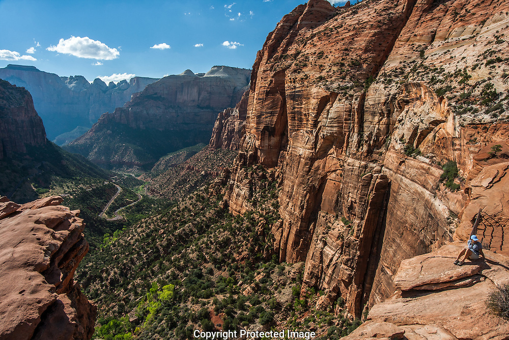 Visitor sits above the Great Arch in Zion National Park