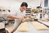 Young male baker making dough in commercial kitchen