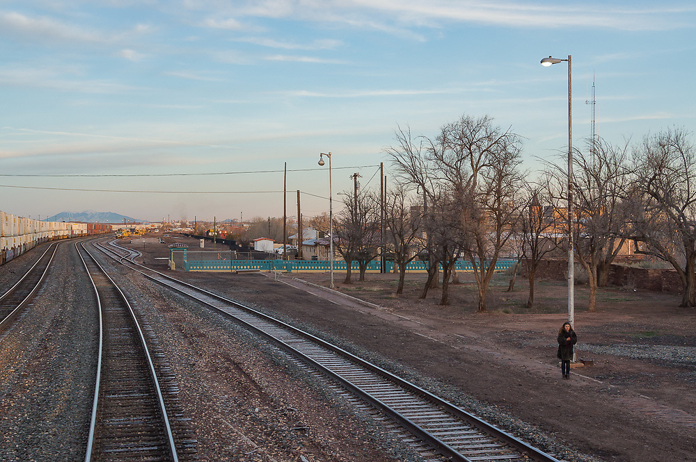 Lone woman standing by the train tracks in the early morning in the cold.