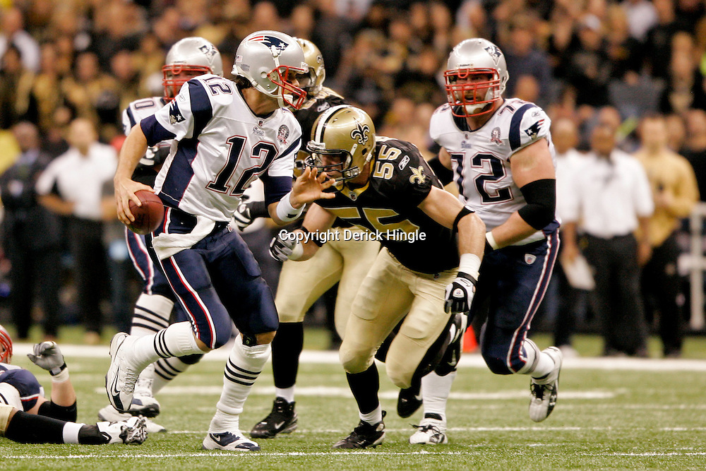 2009 November 30: New England Patriots quarterback Tom Brady (12) is pressured by New Orleans Saints linebacker Scott Fujita (55) during a 38-17 win by the New Orleans Saints over the New England Patriots at the Louisiana Superdome in New Orleans, Louisiana.