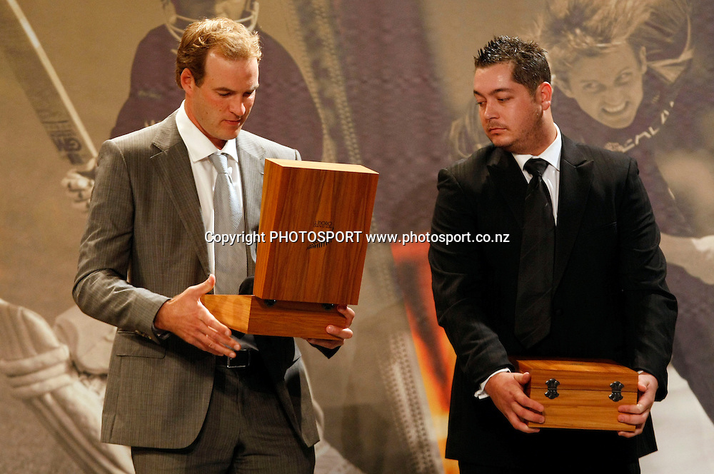 Tim McIntosh looks at his Black Cap as Jesse Ryder looks on.<br />
