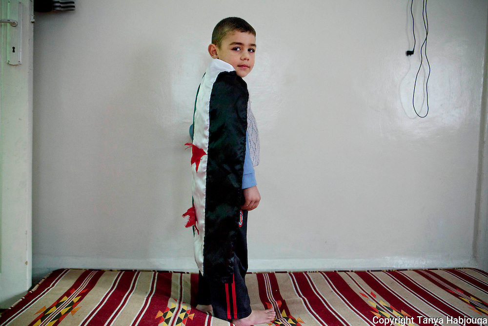 Sufian, 4 years old, and son of torture survivor Abu Khatab. He was small baby on multiple occasions his father was jailed--and did not recognize him on one return home, asking him if he was his father. LIving in a sparse home, the few things hanging in the wall include the orginal Syrian flag previous to Assad regime, which Sufian enjoys playing with.
