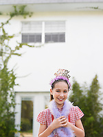 Girl (10-12) in tiara and feather boa standing outside house