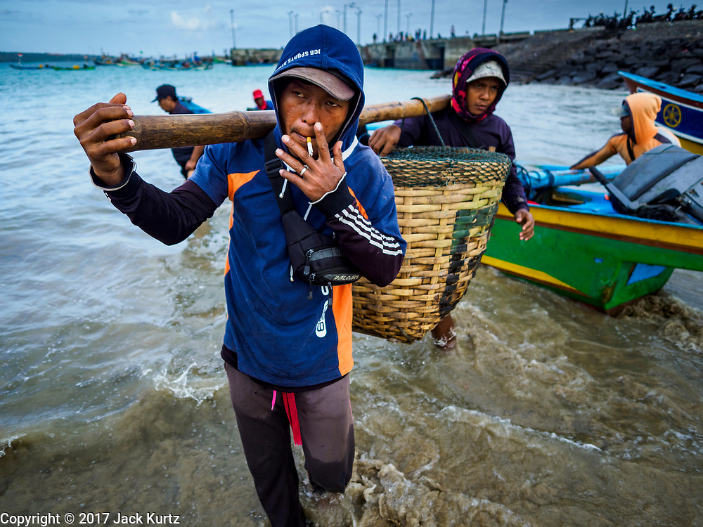 03 AUGUST 2017 - KUTA, BALI, INDONESIA: Men take fish caught on a trawler from a canoe that shuttles crewmen and catch between the trawlers and shore on Jimbrana Beach in Kuta. The beach is close to the airport and a short drive from other beaches in southeast Bali. Jimbrana was originally a fishing village with a busy local market. About 25 years ago, developers started building restaurants and hotels along the beach and land prices are rising. The new emphasis on tourism is changing the nature of the area but the fishermen are still busy very early in the morning.     PHOTO BY JACK KURTZ