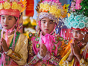 "04 APRIL 2015 - CHIANG MAI, CHIANG MAI, THAILAND:  Boys being ordained as a Buddhist novices pray at Wat Phra Singh during the Poi Song Long Festival in Chiang Mai. The Poi Sang Long Festival (also called Poy Sang Long) is an ordination ceremony for Tai (also and commonly called Shan, though they prefer Tai) boys in the Shan State of Myanmar (Burma) and in Shan communities in western Thailand. Most Tai boys go into the monastery as novice monks at some point between the ages of seven and fourteen. This year seven boys were ordained at the Poi Sang Long ceremony at Wat Pa Pao in Chiang Mai. Poy Song Long is Tai (Shan) for ""Festival of the Jewel (or Crystal) Sons.     PHOTO BY JACK KURTZ"