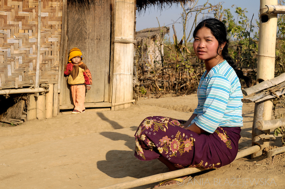 Burma/Myanmar, Shan Mountains. Taung Yo woman sitting near  her house.