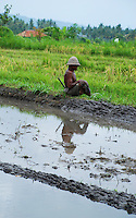 An old farmer is resting after working in his paddy fields - he's being reflected in the water of his irrigation ditch.