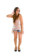 Female teen dances while she enjoys music on her headphones on white background