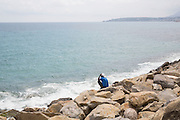 Uno dei migranti accampati sugli scogli di Ventimiglia al confine con la Francia. Ventimiglia, 16 giugno 2015. Guido Montani / OneShot<br /> <br /> One of the migrants displaced on the rocks close to the France-Italy boarder in Ventimiglia. Ventimiglia, 16 june 2015. Guido Montani / OneShot