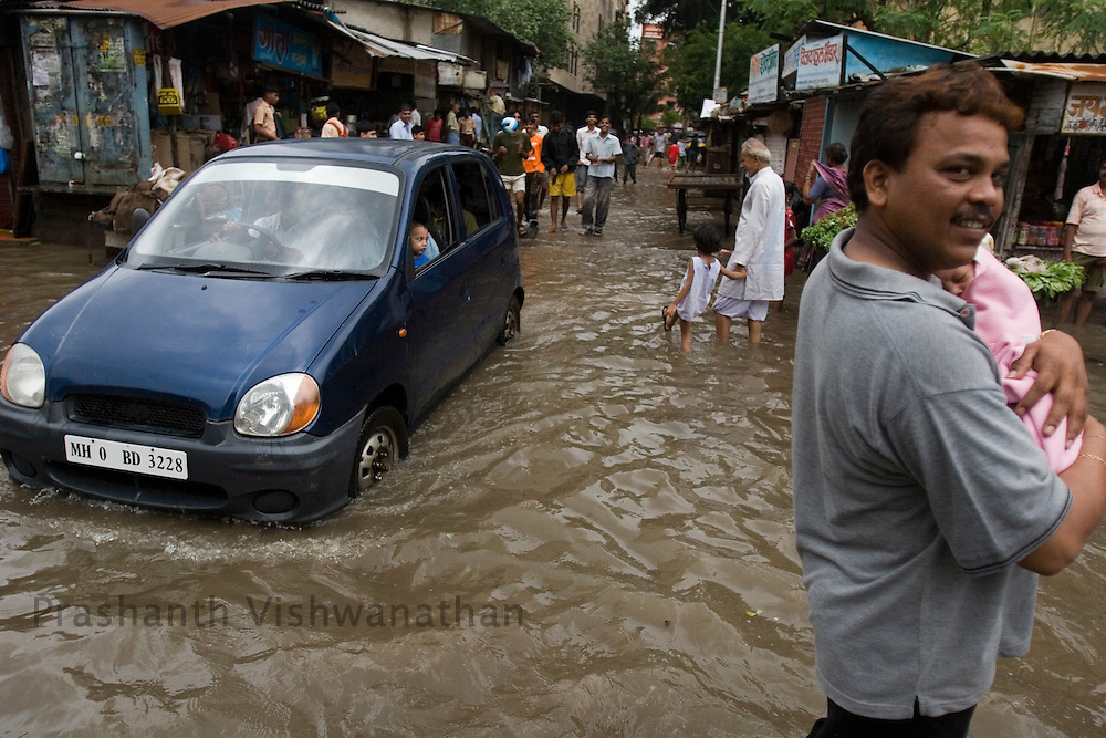 A man carries a baby through a flooded road in Mumbai, India, on Friday July 1, 2008. Photographer:  Prashanth Vishwanathan/Bloomberg News