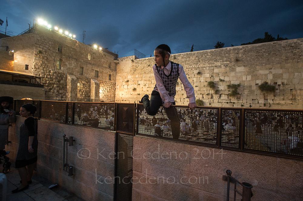 An ultra orthodox Jewish boy plays at the Western Wall during Shabbat in Jerusalem, Israel April, 19, 2014. Photo Ken Cedeno