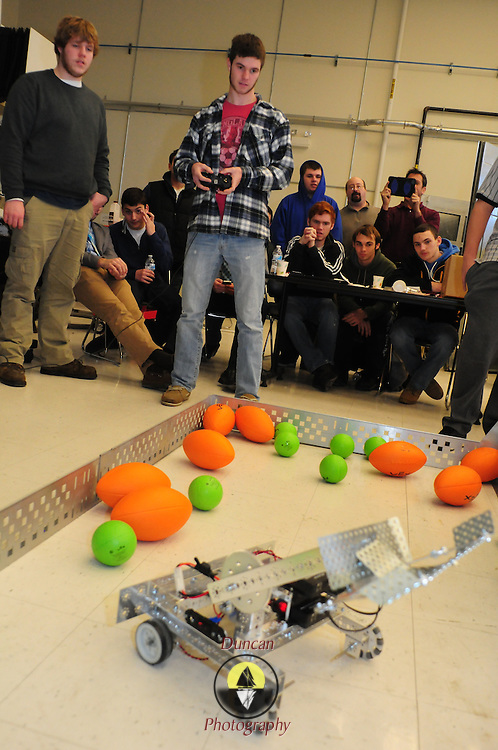 BRUNSWICK, Maine --  12/17/13 -- Pip Butterfield, 17, center, of Kennebunk High School drives his team's competition robot by remote control at Southern Maine Community College (SMCC) last Tuesday. High School Students from Portland, Lewiston and Kennebunk gathered at SMCC's Brunswick center for their first robotics competition. A Bank of America grant to Portland and Lewiston started them up last spring -- giving an opportunity for young adults to work in teams to conceive, build, program and operate the small robots.  Photo © Roger S. Duncan 2013.