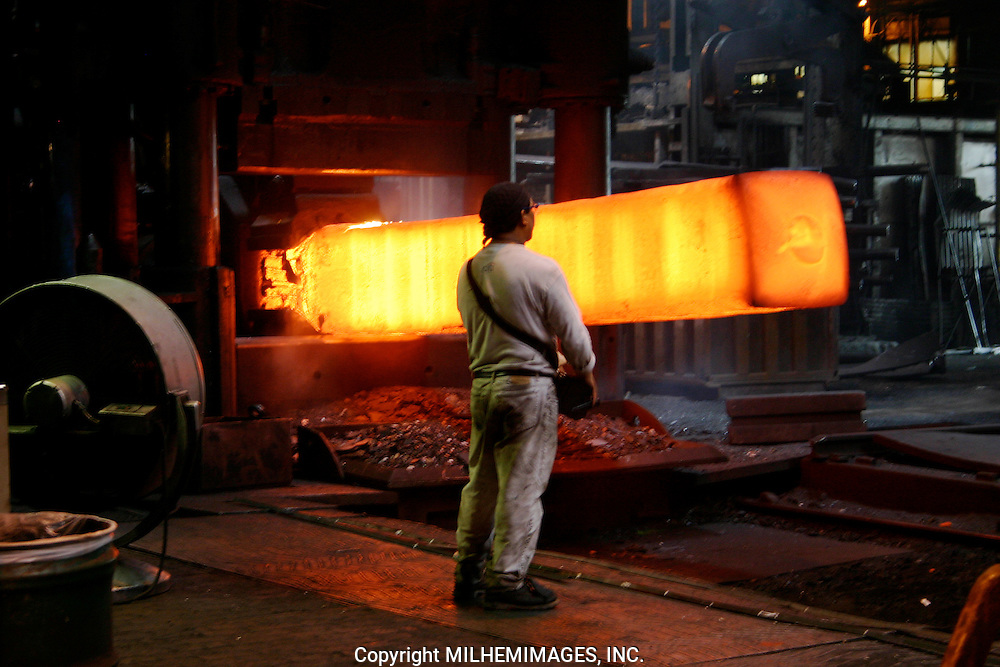Steel worker stands next to hot metal furnace.