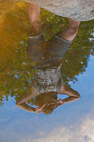 Figure reflected in a pool with blue sky-2