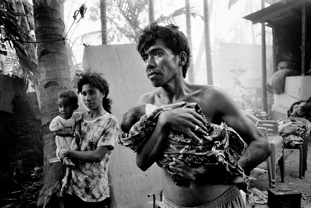 The Guterres family return to the burnt out remains of their home, as rampaging Militia and Indonesian soldiers torch nearby buildings. Dili Timor Leste September 1999 ©David Dare Parker