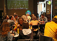 People talk and watch the Iowa football game at a Movember get together during the Iowa football game at Dublin City Pub in Cedar Rapids on Saturday, November 17, 2012.