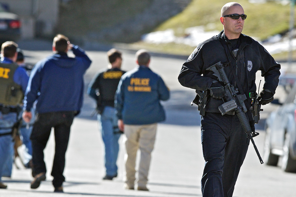 Coeur d'Alene Police Officer Shane Avirett walks toward his vehicle discussing search operations for a fugitive on Tubbs Hill with representatives from the FBI, U.S. Marshall's Office and Kootenai County Sheriff's Department.