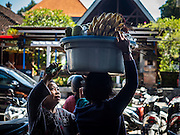10 OCTOBER 2016 - UBUD, BALI, INDONESIA:  A woman carries a pan of bananas in the market in Ubud. The morning market in Ubud is for produce and meat and serves local people from about 4:30 AM until about 7:30 AM. As the morning progresses the local vendors pack up and leave and vendors selling tourist curios move in. By about 8:30 AM the market is mostly a tourist market selling curios to tourists. Ubud is Bali's art and cultural center.     PHOTO BY JACK KURTZ