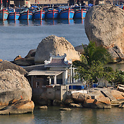 A house house sits in the middle of a fishing harbour in Nha Trang, Vietnam.