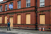 A man walks past a boarded up and closed down magistrates court, Whitley Bay,  Northumberland. UK. (photo by Andrew Aitchison / In pictures via Getty Images)