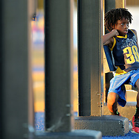 Jahree Garth, 9, of Tupelo, watches the Tupelo football team go through warm up drills as he sits on a bleacher ubder the scoreboard Friday night.