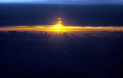 Setting sun peaks through a narrow horizontal break in a bank of clouds.