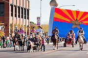 28 JANUARY 2012 - BUCKEYE, AZ:    Participants ride their horses in front of large inflatable Arizona flag during the Buckeye Days parade. The Buckeye Days parade went through downtown Buckeye, AZ, an agricultural community about 45 miles west of Phoenix. The parade was one the first events to mark Arizona's centennial celebration. Arizona was admitted to the United States on Feb 14, 1912, making it the 48th state in the union. The state celebrates its 100th birthday with a series of events on Feb. 14, 2012.    PHOTO BY JACK KURTZ