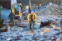 © Licensed to London News Pictures. 18/03/2016. Cumbria UK. File picture shows a man walking down a completely destroyed road in Glenridding damaged by storms last December. The Department for Transport has pledged an additional £82.6m today to fund essential repairs to infrastructure in Cumbria damaged by Storms Desmond & Eva last December. Photo credit: Andrew McCaren/LNP