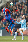 Crystal Palace forward Christian Benteke (17) jumps for a header as Manchester City midfielder David Silva (21) defends during the Premier League match between Crystal Palace and Manchester City at Selhurst Park, London, England on 14 April 2019.