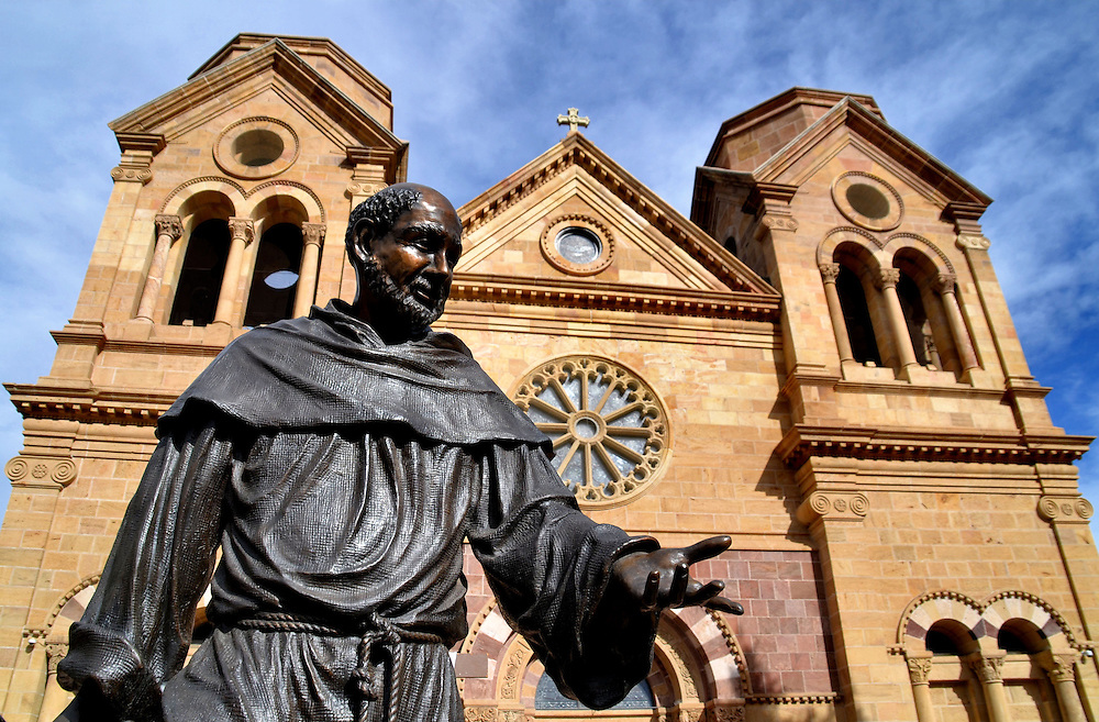 Cathedral Basilica of St. Francis of Assisi in Santa Fe, New Mexico<br /> When Santa Fe, New Mexico, was founded in 1610, its name in English was The Royal Town of the Holy Faith of St. Francis of Assisi. Therefore, it was appropriate the Cathedral Basilica of St. Francis of Assisi was placed downtown in 1886. The structure was built with yellow sandstone blocks in a Romanesque Revival style. This western entrance features arches, columns, a rose window and two towers. The statue of the patron saint of animals was added in 1967.