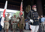 Japanese nationalists dressed in World War II and Edo-preriod military costume line up by the main gate of Yasukuni Shrine in Tokyo, Japan. very year on August 15, the day Japan officially surrendered in WWII, tens of thousands of Japanese visit the controversial shrine to pay their respects to the 2.46 million war dead enshrined there, the majority of which are soldiers and others killed in WWII and including 14 Class A convicted war criminals, such as Japan's war-time prime minister Hideki Tojo. Each year speculation escalates as to whether the country's political leaders will visit the shrine, the last to do so being Junichiro Koizumi in 2005. Nationalism in Japan is reportedly on the rise, while sentiment against the nation by countries that suffered from Japan's wartime brutality, such as China, has been further aggravated by Japan's insistence on glossing over its wartime atrocities in school text books..Photographer:Robert Gilhooly.
