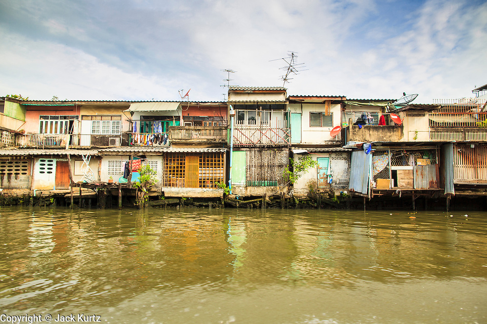 """17 NOVEMBER 2012 - BANGKOK, THAILAND:  Traditional housing along a canal in the Thonburi section of Bangkok. Bangkok used to be known as the """"Venice of the East"""" because of the number of waterways the criss crossed the city. Now most of the waterways have been filled in but boats and ships still play an important role in daily life in Bangkok. Thousands of people commute to work daily on the Chao Phraya Express Boats and fast boats that ply Khlong Saen Saeb or use boats to get around on the canals on the Thonburi side of the river. Boats are used to haul commodities through the city to deep water ports for export.    PHOTO BY JACK KURTZ"""