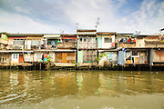 "17 NOVEMBER 2012 - BANGKOK, THAILAND:  Traditional housing along a canal in the Thonburi section of Bangkok. Bangkok used to be known as the ""Venice of the East"" because of the number of waterways the criss crossed the city. Now most of the waterways have been filled in but boats and ships still play an important role in daily life in Bangkok. Thousands of people commute to work daily on the Chao Phraya Express Boats and fast boats that ply Khlong Saen Saeb or use boats to get around on the canals on the Thonburi side of the river. Boats are used to haul commodities through the city to deep water ports for export.    PHOTO BY JACK KURTZ"