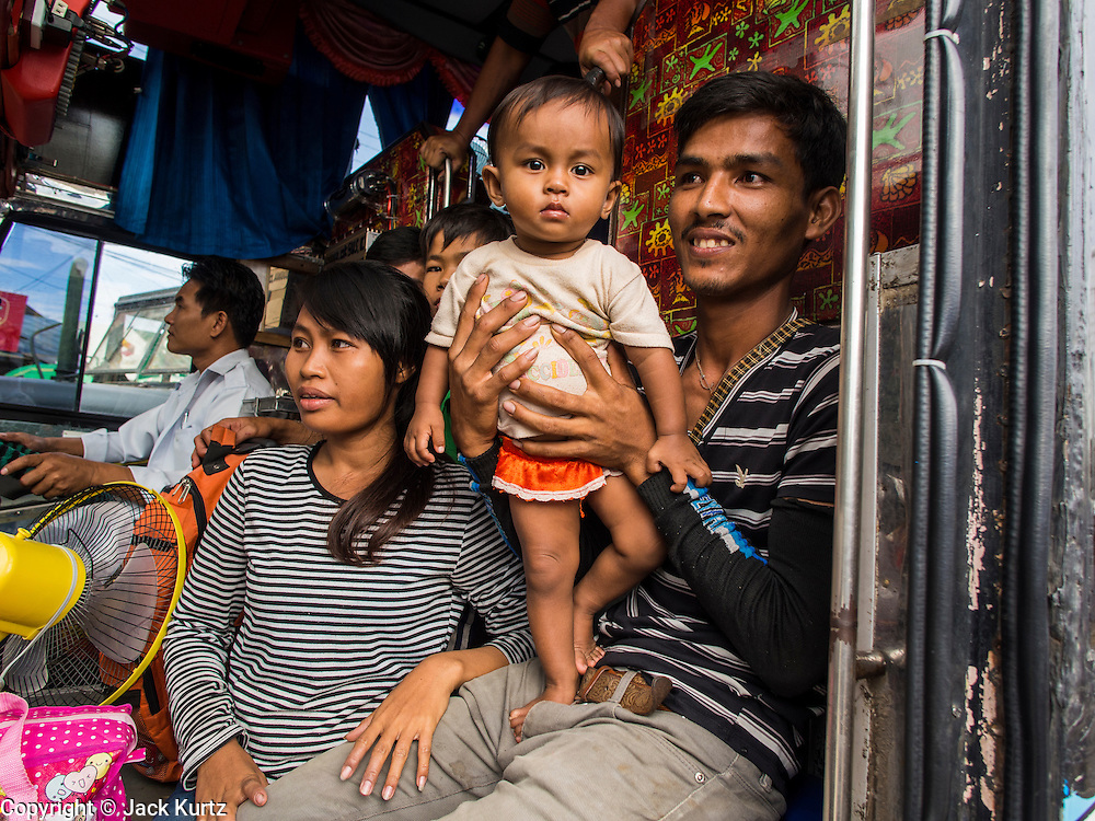 16 JUNE 2014 -  POIPET, CAMBODIA: Cambodian migrants in a bus coming into Poipet, Cambodia. More than 150,000 Cambodian migrant workers and their families have left Thailand since June 12. The exodus started when rumors circulated in the Cambodian migrant community that the Thai junta was going to crack down on undocumented workers. About 40,000 Cambodians were expected to return to Cambodia today. The mass exodus has stressed resources on both sides of the Thai/Cambodian border. The Cambodian town of Poipet has been over run with returning migrants. On the Thai side, in Aranyaprathet, the bus and train station has been flooded with Cambodians taking all of their possessions back to Cambodia.     PHOTO BY JACK KURTZ