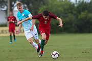 Portugal defender Francisco Silva (5) breaks away from a tackle from Slovenia midfielder Matjaz Kamensek (15) during a CONCACAF boys under-15 championship soccer game, Sunday, August 11, 2019, in Bradenton, Fla. Portugal defeated Slovenia in the final in 2-0. (Kim Hukari/Image of Sport)