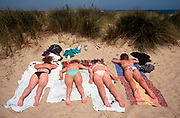 Four young women sunbathe in their bikinis in coastal dunes, on 25th May 1992, in Great Yarmouth, Suffolk, England. (Photo by Richard Baker / In Pictures via Getty Images)