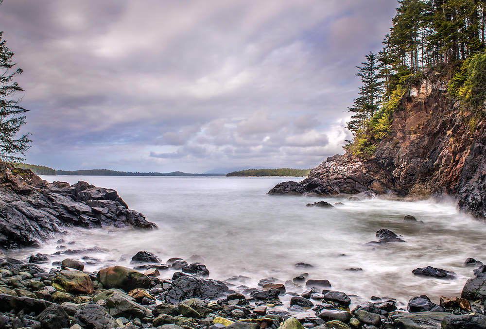 The ruggedness of the West Coast of Vancouver Island is mesmerising. Tell trees and rough, jagged, rocky headlands are everywhere. It was a rainy morning and we hiked out of the town of Tofino and along the trail that hugged the beach. We went for a few hours and reached this rocky cover, the trail ended here. the rain had stopped, but left some moisture on everything, it was a little windy, but I was protected in the cove. An unforgettable Pacific Northwest scene.