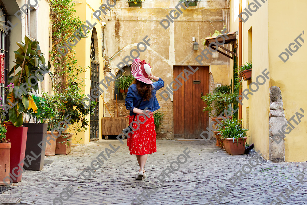 Back view of tourist woman standing and holding hat at Trastevere in Rome, Italy.