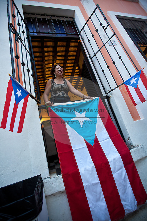 A women watches the parade from her balcony decorated with Puerto Rican flags in Old San Juan January 13, 2011 during the Festival of San Sebastian in San Juan, Puerto Rico.