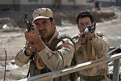 © Licensed to London News Pictures. 09/03/2015. Erbil, Iraq. Kurdish peshmerga fighters cover a building entrance with their Kalashnikov rifles during an urban warfare training session run by German soldiers at a partially finished housing estate near Erbil, Iraq. <br /> <br /> The training is part of a four week platoon level infantry training package run by coalition forces aimed at improving the efficiency of the Iraqi Security Forces. Photo credit: Matt Cetti-Roberts/LNP
