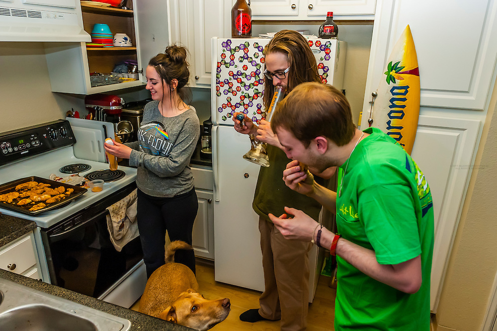 Young people smoking marijuana in a bong in their kitchen, Aurora, Colorado USA. Colorado was the first state to legalize the sale of marijuana for recreational use in 2014.