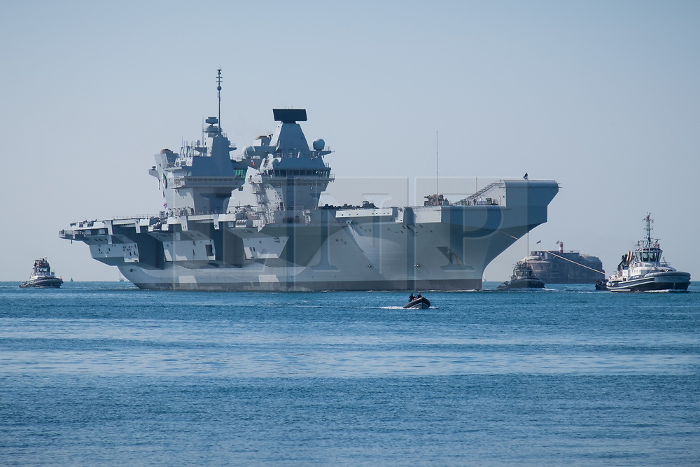 © Licensed to London News Pictures. 23/06/2018. Portsmouth, UK.  The Royal Navy's flagship, HMS Queen Elizabeth, sailing into Her Majesty's Naval Base (HMNB) Portsmouth this morning, 23rd June 2018.  The aircraft carrier has been performing trials in the Northern Atlantic, including her first replenishment at sea. She is expected to remain in Portsmouth ahead of aircraft trials off the coast of the United States later this summer.Photo credit: Rob Arnold/LNP