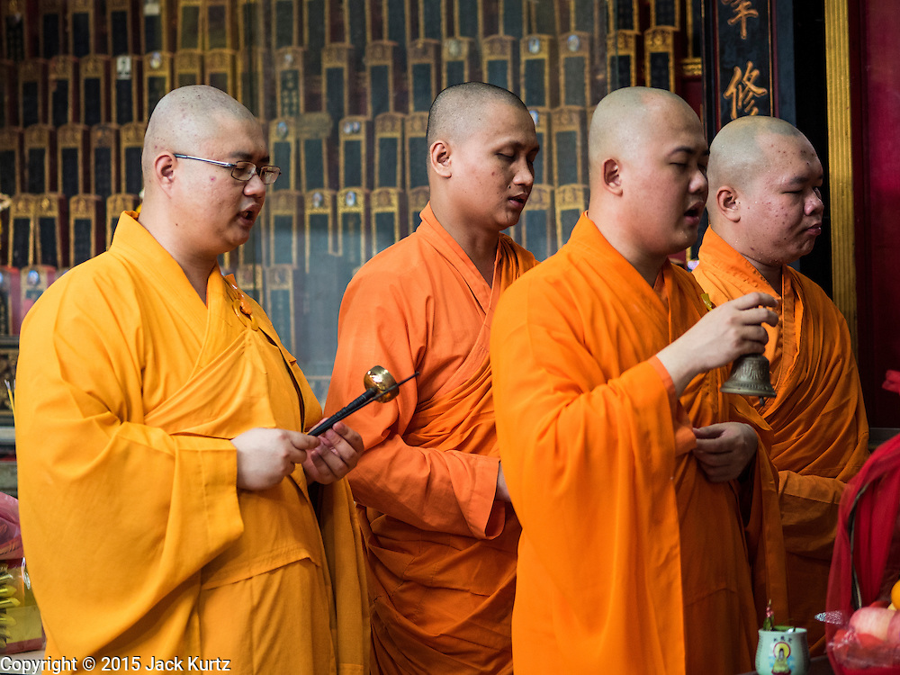 28 AUGUST 2015 - BANGKOK, THAILAND: Mahayana monks lead a service on Hungry Ghost Day at Wat Mangkon Kamalawat in the Chinatown section of Bangkok. Wat Mangkon Kamalawat is the largest Mahayana Buddhist temple in Chinatown. Mahayana  Buddhists believe that the gates of hell are opened on the full moon of the seventh lunar month of the Chinese calendar, and the spirits of hungry ghosts allowed to roam the earth. These ghosts need food and merit to find their way back to their own. People help by offering food, paper money, candles and flowers, making merit of their own in the process. Hungry Ghost Day is observed in communities with a large ethnic Chinese population, like Bangkok's Chinatown.      PHOTO BY JACK KURTZ